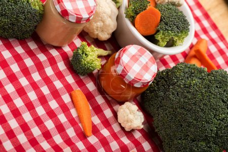 Photo for High angle view of broccoli, carrots and cauliflower near jars of baby food on tablecloth on wooden background - Royalty Free Image