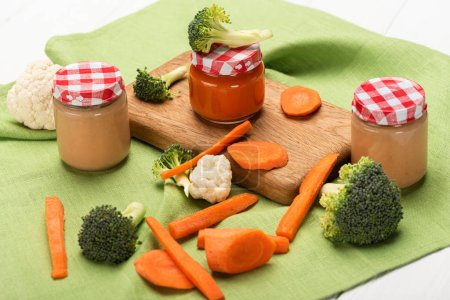 Photo for Jars of baby food with ripe carrots, broccoli and cauliflower on napkin on white wooden background - Royalty Free Image