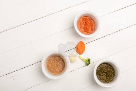 Photo for Top view of carrot slices, pieces of cauliflower and broccoli near bowls with baby food on white wooden surface - Royalty Free Image