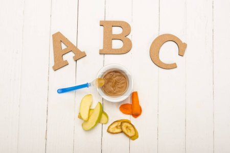 Photo for Top view of bowl with baby nutrition and spoon, ingredients and wooden letters on white wooden surface - Royalty Free Image