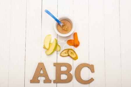 Foto de Vista superior de los ingredientes frescos cerca de alimentos para bebés y letras de madera en la superficie de madera blanca. - Imagen libre de derechos