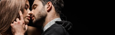 Photo for Panoramic shot of handsome man kissing attractive woman isolated on black - Royalty Free Image
