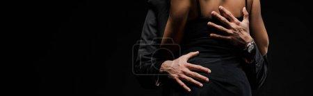 Photo pour Plan panoramique de l'homme touchant les fesses de la femme en robe isolé sur noir - image libre de droit