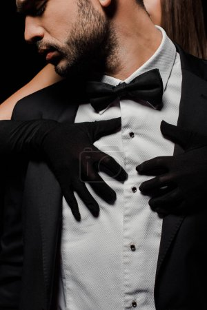 Photo for Young woman in gloves hugging man in suit isolated on black - Royalty Free Image