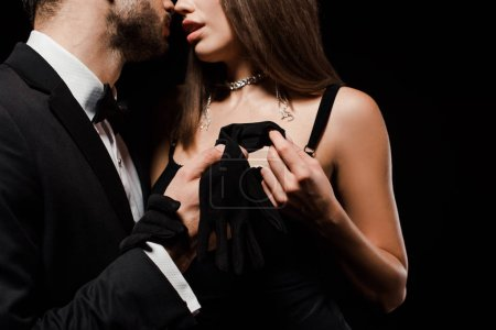 Photo for Cropped view of man holding glove near hot woman isolated on black - Royalty Free Image