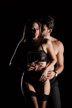 leidenschaftlicher Mann umarmt attraktive Frau in Spitzenunterwäsche isoliert auf schwarz