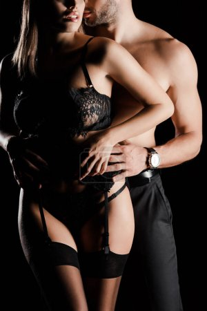 cropped view of passionate man touching woman in lace underwear isolated on black