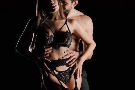 vue recadrée de musclé homme toucher femme en dentelle sous-vêtements isolé sur noir