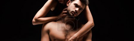 Photo pour Panoramic shot of passionate woman touching shirtless man isolated on black - image libre de droit