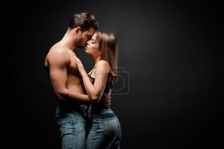 Photo for Side view of muscular man kissing seductive girl on black - Royalty Free Image