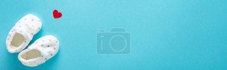 Photo pour Photographie panoramique de bottes de bébé avec du papier en forme de coeur sur fond bleu, concept des mères jour - image libre de droit