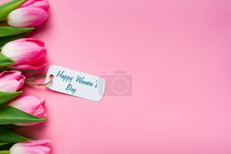 Photo for Top view of happy womens day lettering on paper label with row of tulips on pink background - Royalty Free Image
