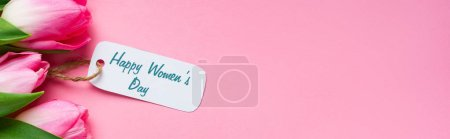 Photo for Top view of happy womens day lettering on paper label with tulips on pink surface, panoramic shot - Royalty Free Image