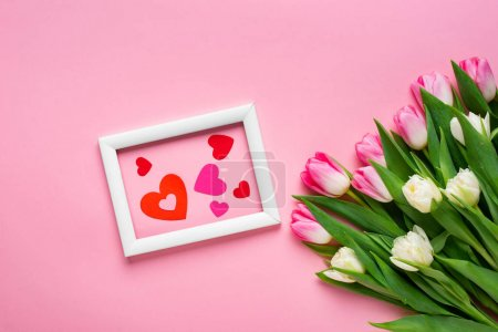 Top view of paper hearts in frame near bouquet of ...