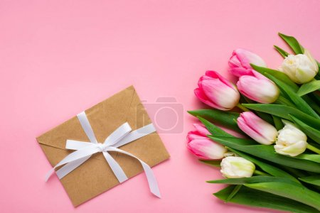 Photo for Top view of envelope with bow and bouquet of tulips on pink surface - Royalty Free Image