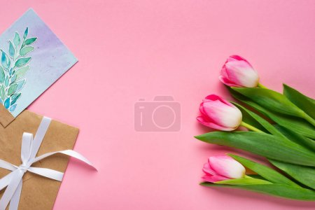 Photo for Top view of envelope, greeting card and tulips on pink background - Royalty Free Image