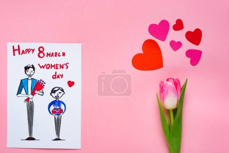 Photo for Top view of greeting card with drawing and 8 march happy womens day lettering and tulip with paper hearts on pink background - Royalty Free Image