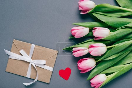 Photo for Top view of envelope with bow, paper heart and bouquet of tulips on grey background - Royalty Free Image