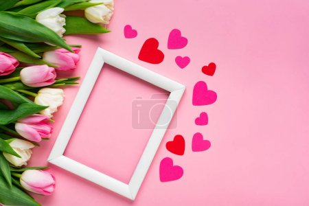Photo for Top view of white frame with paper hearts and bouquet of tulips on pink surface - Royalty Free Image