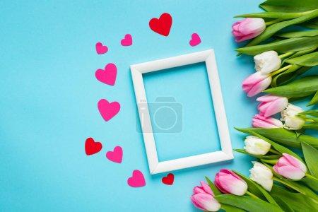 Foto de Vista superior del marco blanco vacío con corazones de papel y tulipanes en fondo azul. - Imagen libre de derechos
