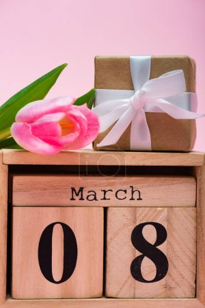 Photo for Close up view of gift box tulip on wooden calendar with 8 march date on pink background - Royalty Free Image