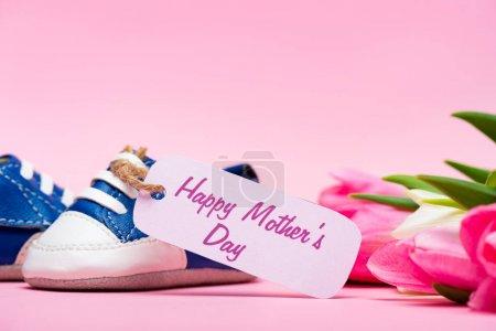 Photo pour Vue rapprochée des chaussons bébé avec lettrage heureux de la fête des mères sur l'étiquette en papier près des tulipes sur fond rose - image libre de droit