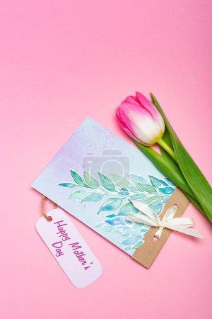 Photo pour Vue du dessus du dessin carte de vœux avec joyeux lettrage de la fête des mères sur étiquette en papier et tulipe sur fond rose - image libre de droit