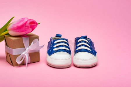 Baby booties, gift box and tulip on pink background, concept of mothers day