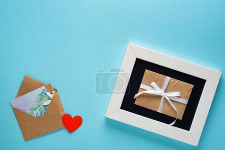 Photo for Top view of envelopes with drawing greeting card near chalkboard on blue background - Royalty Free Image