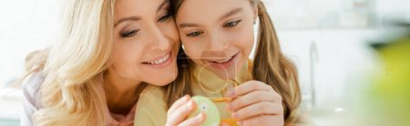 Photo for Panoramic shot of cute kid painting easter egg near happy mother - Royalty Free Image
