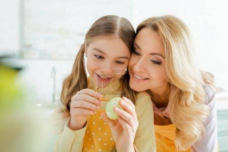 Photo pour Foyer sélectif de la mère heureuse près de sa fille peinture oeuf de Pâques - image libre de droit