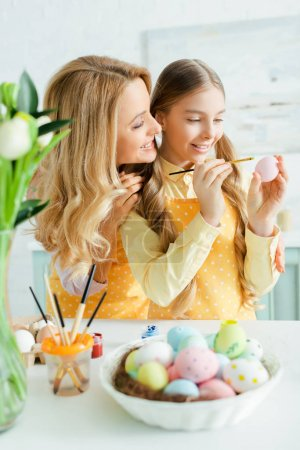 Photo for Selective focus of cheerful kid painting easter egg near mother - Royalty Free Image