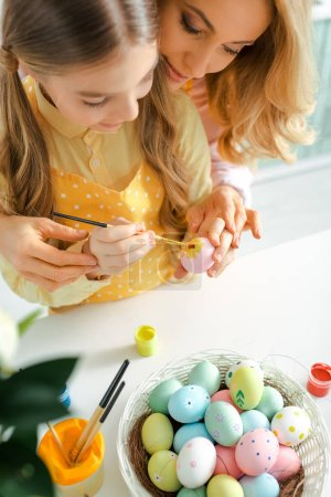 Photo for Overhead view of kid painting easter egg near mother - Royalty Free Image