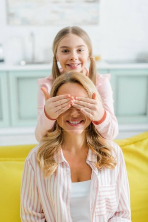 Photo for Selective focus of happy kid covering eyes of cheerful mother - Royalty Free Image