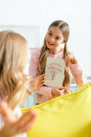 Photo for Selective focus of happy daughter holding greeting card with happy mothers day lettering near mother - Royalty Free Image