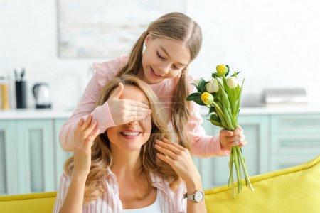 Photo pour Enfant heureux couvrant les yeux de la mère gaie tout en tenant bouquet de tulipes - image libre de droit