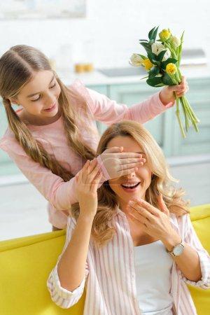 Photo pour Mignon enfant couvrant les yeux de la mère gaie tout en tenant bouquet de tulipes - image libre de droit