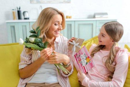Foto de Jovencito alegre presentación de regalos y tarjeta de felicitación con las madres felices día de la carta cerca de la madre. - Imagen libre de derechos