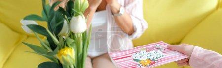 Photo pour Photo panoramique d'un enfant tenant des tulipes et une carte de souhaits avec des mères heureuses lettrage de jour près de la mère - image libre de droit