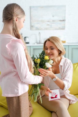 Photo for Happy mother looking at tulips while holding greeting card near daughter - Royalty Free Image