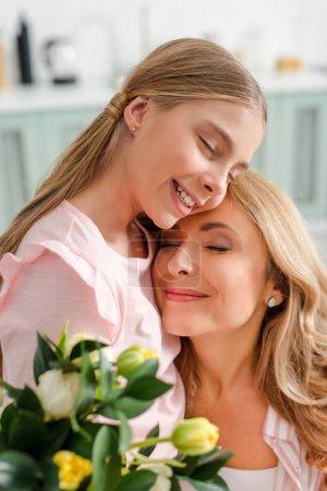 Photo pour Foyer sélectif de mère heureuse et sa fille souriant près des tulipes - image libre de droit