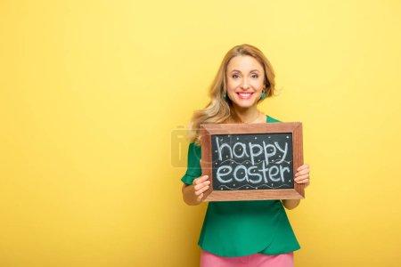 Photo pour Femme heureuse tenant tableau noir avec joyeuse Pâques lettrage isolé sur jaune - image libre de droit