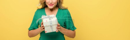 Photo for Panoramic shot of cheerful woman holding gift box isolated on yellow - Royalty Free Image