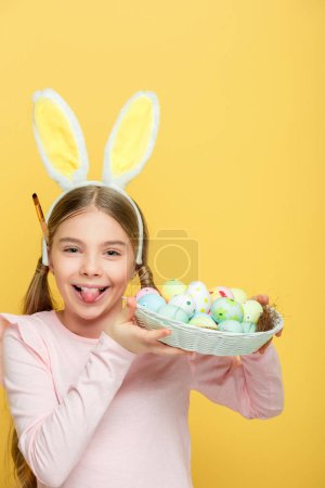 Photo pour Jeune garçon gai aux oreilles nues sortant de la langue et tenant des œufs de Pâques dans un panier isolé sur jaune - image libre de droit