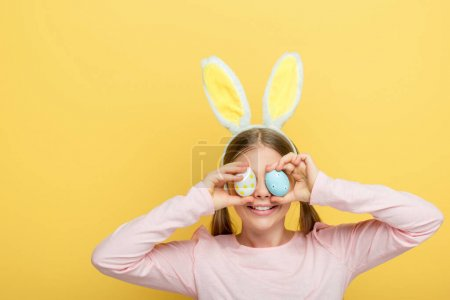 Photo for Happy child with bunny ears covering eyes with easter eggs isolated on yellow - Royalty Free Image