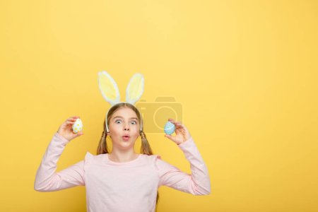 Photo for Shocked child with bunny ears holding painted easter eggs isolated on yellow - Royalty Free Image