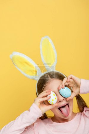 Photo for Kid with bunny ears sticking out tongue and covering eyes with easter eggs isolated on yellow - Royalty Free Image