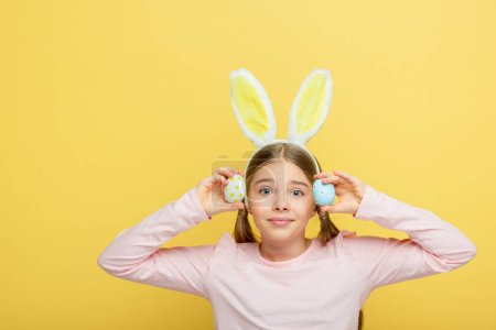 Photo for Cute child with bunny ears holding painted easter eggs isolated on yellow - Royalty Free Image