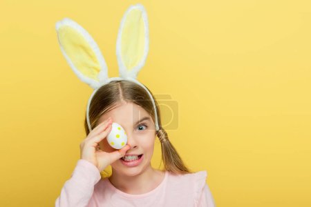 Photo pour Enfant émotionnel avec des oreilles nues recouvrant les yeux avec des œufs de Pâques en pointes isolés sur jaune - image libre de droit