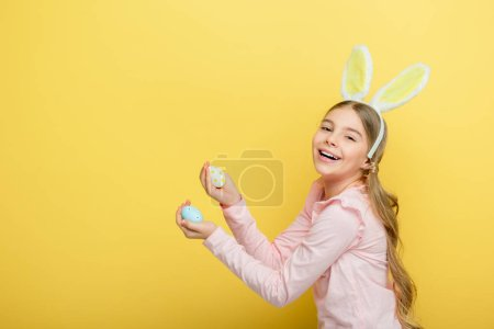 Photo for Positive child with bunny ears holding painted easter eggs isolated on yellow - Royalty Free Image